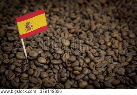 Spain Flag Sticking In Roasted Coffee Beans. The Concept Of Export And Import Of Coffee