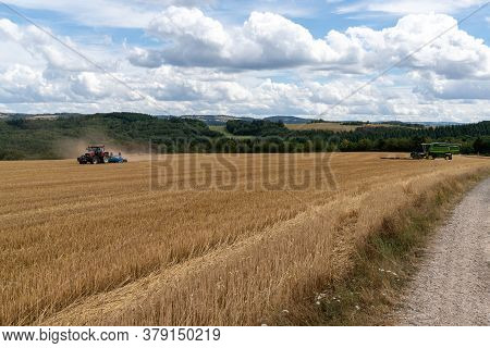Oberbrombach, Rp / Germany - 26 July 2020: Red Tractor Pulling A Blue Field Cultivator Across A Harv