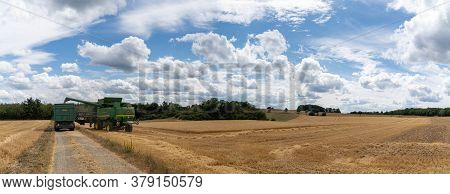 Oberbrombach, Rp / Germany - 26 July 2020: A Green Combine Harvester Unloading Cut Wheat Crop Into A