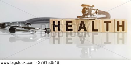 Health The Word On Wooden Cubes, Cubes Stand On A Reflective White Surface, On Cubes - A Stethoscope
