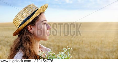 Profile Portrait Of A Young Woman In A Straw Hat And With A Bouquet Of Wild Flowers In A Wheat Field