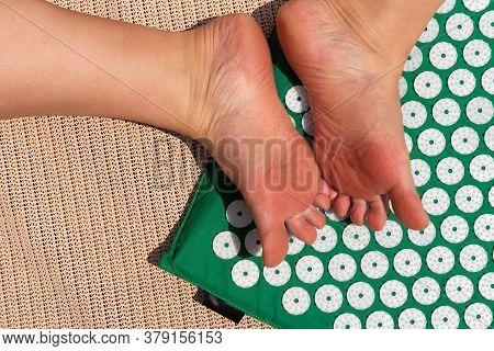 Female Feet Standing On Acupressure Mat. Self Acupuncture Massage.