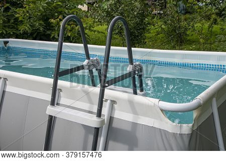 Home Outdoor Pool Filled With Water With A Plastic Ladder For Descent.