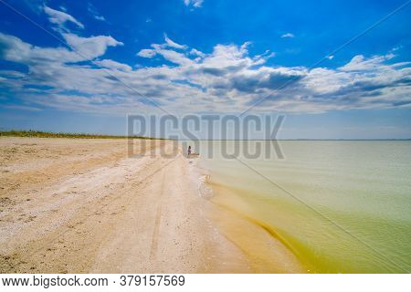 A Lonely Young Woman Sits On The Sand At The Surf Line On An Empty Sea Beach.  Bright Sunny Summer D