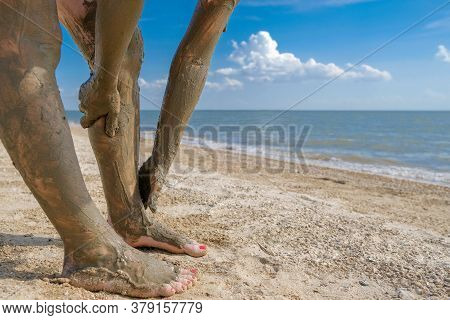 Selective Focus On Beautiful Female Foot With Bright Red Pedicure On The Beach Sand.  Hands Smear He
