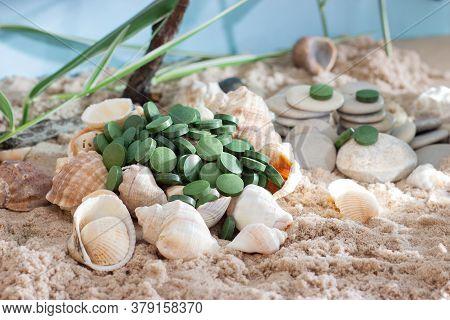 Spirulina Or Chlorella Tablets And Powder Among Shells, Rocks And Sand. Superfood Concept.