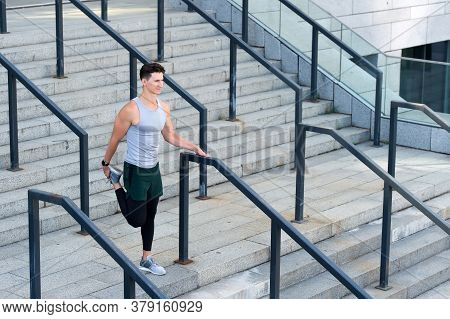 Runner In Sportswear Warming Up. Training On Fresh Air. Athletic Young Man Stretching His Legs Muscl