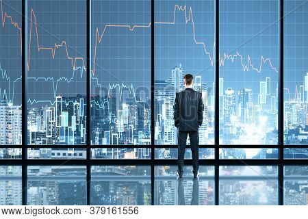 Businessman Standing In Office Interior With Glowing Forex Chart Hologram. Trade And Stats Concept.