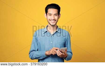 Asian Man Holding Mobile Phone Smiling While Standing Isolated On Yellow Background, People On Smart