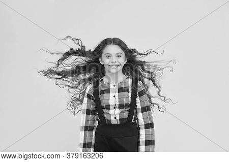 Pure Beauty For Your Hair. Happy Kid With Wavy Long Hair. Little Child With Flying Hair Yellow Backg