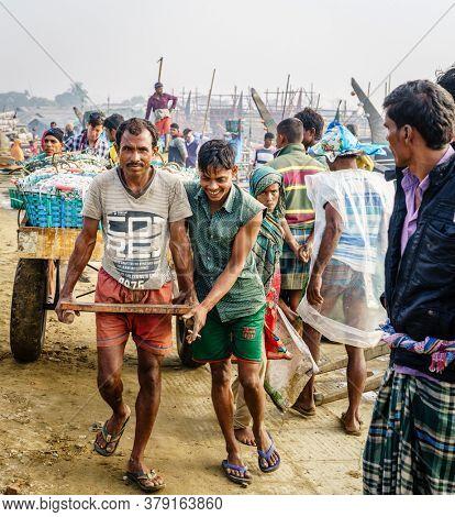Chittagong, Bangladesh, December 23, 2017: Fishermen are pulling cart with fresh catch of shrimp at a market in Chittagong, Bangladesh