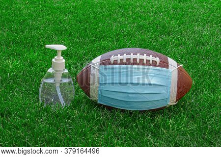 An American Football With A Facemask And Hand Sanitizer On Field With Green Grass. Concept Football