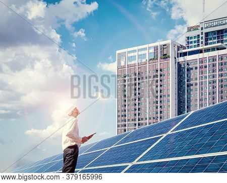 An Engineer Stood In A Solar Power Plant And In His Hand Held A Laptop, He Looked At The Tall Buildi