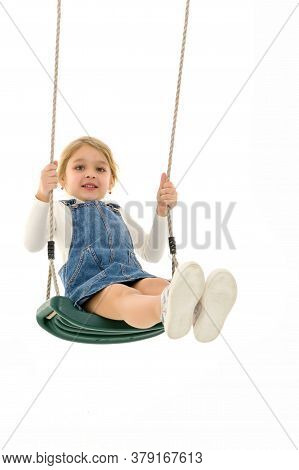 Full Length Shot Of Cute Girl Swinging On Rope Swing, Lovely Blonde Kid Wearing White Blouse And Den