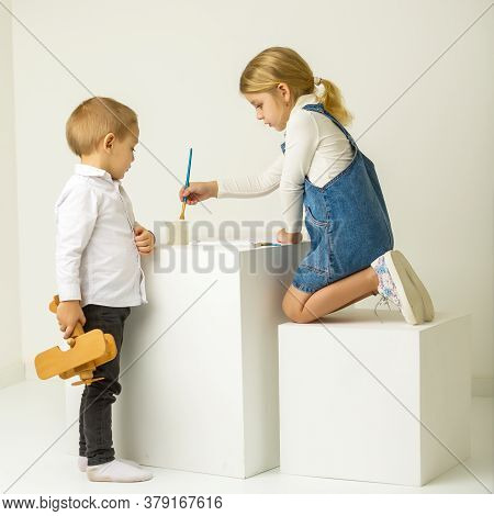 Cute Blonde Girl Sitting On Her Knees And Painting With Paintbrush, Her Brother Looking At Her With