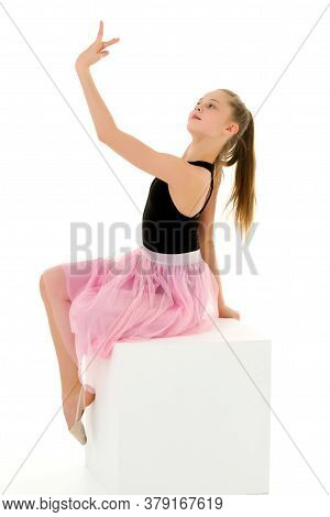 Thoughtful Beautiful Girl Sitting On A White Cube, Portrait Of A Cute Preteen Girl Posing In The Stu