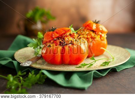 Delicious stuffed tomatoes in shape of pumpkin with rice, vegetables and meat. Concept homemade healthy eating.