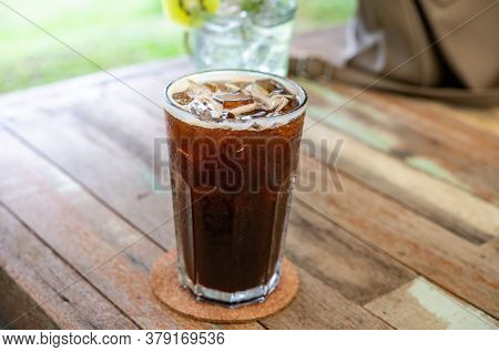 Americano Coffee, Delicious, Sweet, Fragrant In A Glass Of Cold Ice On A Wooden Floor. Photos Jpg