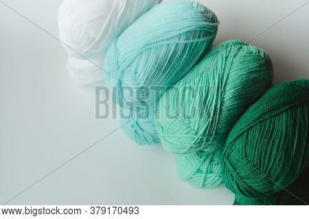 Acrylic Soft Pastel Green, Azure And White Colored Wool Yarn Thread Skeins Row On White Background,