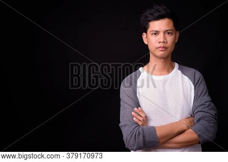 Portrait Of Young Asian Man Against Black Background
