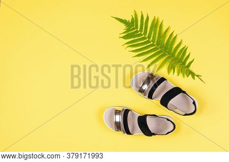 Top View Of Black And White Sandals And A Palm Leaf On A Yellow Background. Concept Of Recreation By