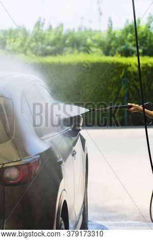 Car's Right Side Being Washed With A High Pressure Water Spray Wand On An Out Of Focus Background. C