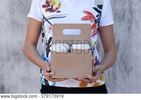 Woman Hands Holding A Paper Cup Holder Close-up. Concept: Food Delivery. Takeaway. Drinks To Go.