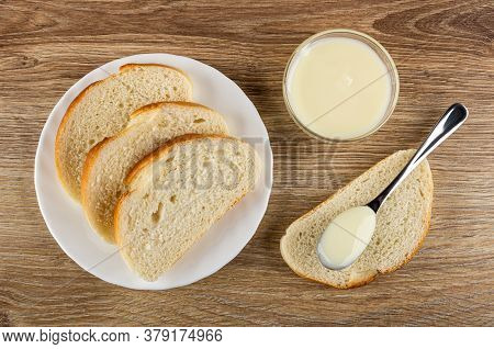 Slices Of Wheat Bread In White Plate, Transparent Glass Bowl With Condensed Milk. Teaspoon With Milk