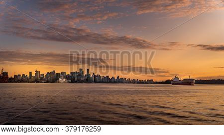 Sunset Over The Skyline Of Downtown Vancouver With A Ocean Freighter Moored In The Harbor. Viewed Fr