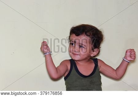 Indoors Baby Shaking Both His Hands, Happy Child Portrait, Close Up Of Child Image