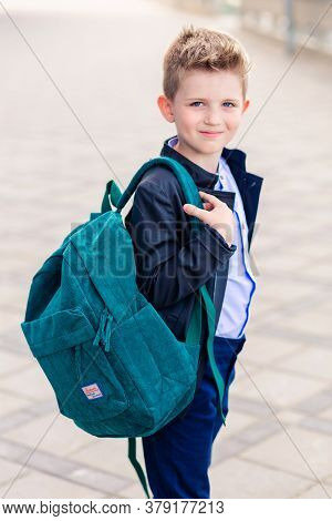 Minsk, Belarus - August 27, 2019. A Boy In A Stylish Suit And With A Backpack On His Back Turns Arou