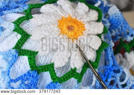 A Close Up Image Of A Crochet Flower On A Vintage Style Doily With A Single Metal Crochet Hook.