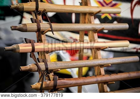 Traditional Native American Indian Handmade Wood Carved Flutes Of Different Sizes On Display For Sal