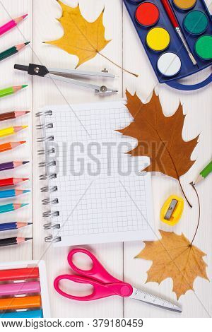 Office Accessories And Orange Leaves On White Boards, Copy Space For Text In Notepad, Back To School
