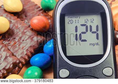 Glucometer For Checking Sugar Level And Heap Of Candies With Cookies. Diabetes And Reduction Of Eati