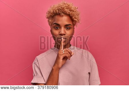Emotional Surprised Dark Skinned Student Makes Hush Gesture, Asks Be Quiet, Has Scared Expression As