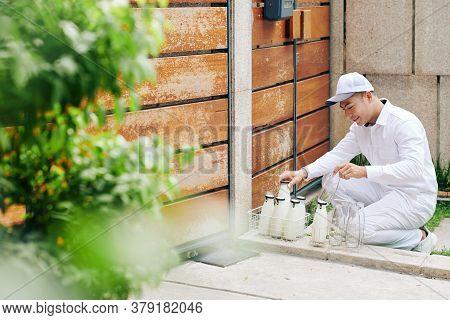 Smilng Handsome Vietnamese Milkman Delivering Milk And Taking Back Empty Glass Bottles
