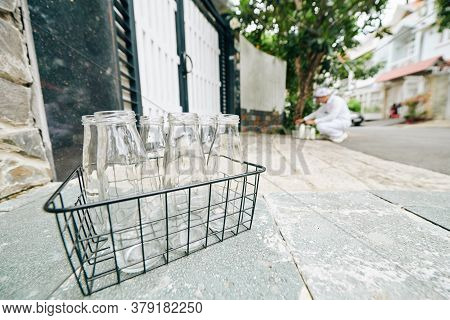 Wire Crate With Empty Glass Bottles And Milkman Putting Bottles With Fresh Milk In Front Of Customer