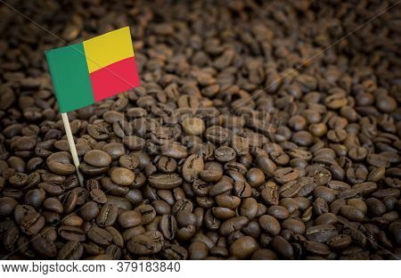 Benin Flag Sticking In Roasted Coffee Beans. The Concept Of Export And Import Of Coffee