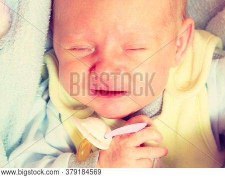 Infant Care, Teething Pain, Colic Ache Concept. Little Newborn Baby Crying In Bed Surrounded With Bl
