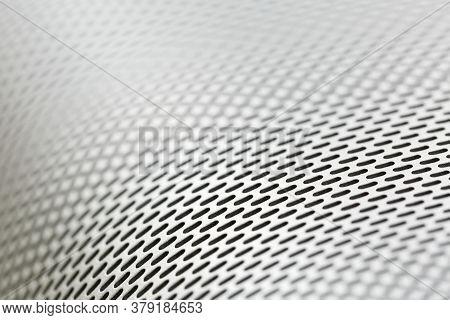 Abstract Background Macro Shot Of Shiny Aluminium Metal Sheet With Holes, Selective Focus