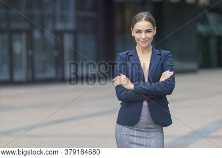 Happy Positive Young Businesswoman In Formal Suit Standing Outdoors Business Centre With Her Hands,
