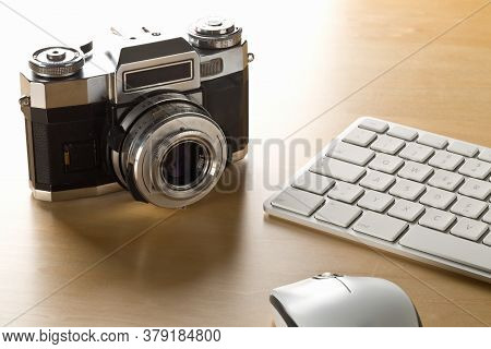 Retro Analog Slr Camera Next To Computer Keyboard And Mouse On Wooden Desk In Office, Digital Photog