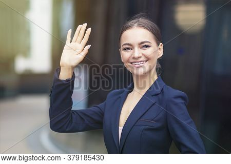 Formal Dressed Happy Businesswoman Is Waving Her Hand Outdoors, Look At Camera, Smiling. Young Offic
