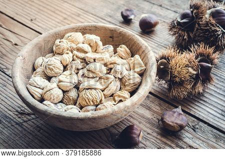 Dried Pilled Chestnuts And Helicons On Wooden Background. European Species Sweet Chestnut Castanea S