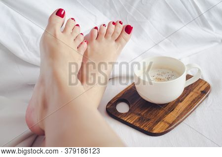 Sexy Woman Relaxing On Bed With Cup Of Hot Coffee Cappuccino. Young Woman With Beautiful Skin And Pe