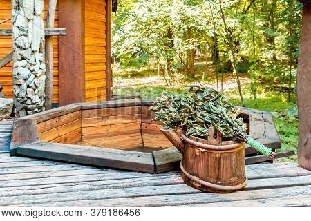 Bath And Sauna. Wooden Bathhouse With Bucket And Broom. Traditional Hygiene. Outdoor
