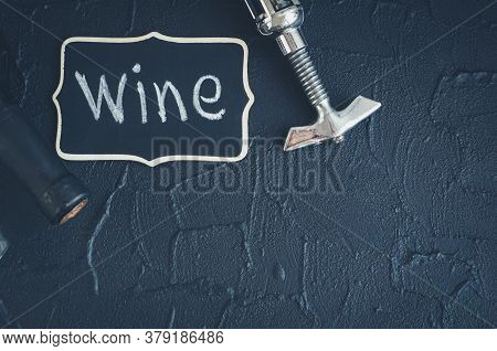 Bottle Of Wine With Corkscrew On Black Stone Background. Traditional Winemaking And Wine Tasting Con