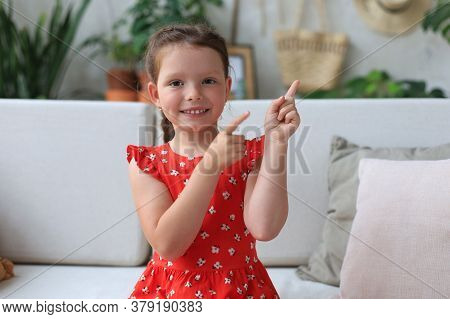 Cute Little Girl Sitting On Cozy Sofa And Pointing Up On Something Intresting By Fingers.