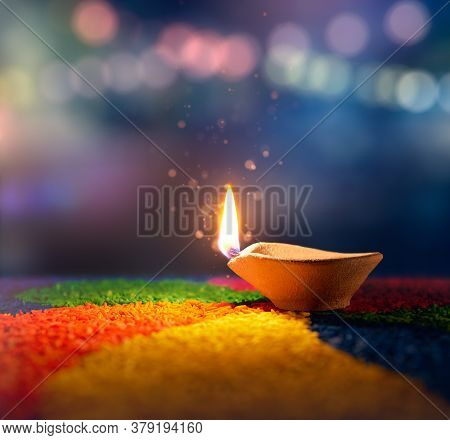 Happy Diwali, Lit Diya Lamp On An Abstract Background With Shallow Depth Of Field
